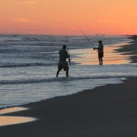"Surf fishing is a popular sport as well as a form of relaxation…as the sun goes down.  ""It don't matter if it's day or night…the best time to fish is when it's rainin' and when it ain't.""  (Photo by Cheryl Mansfield)"