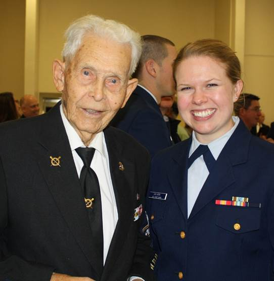 """Retired Coast Guard Chief Ira Lewis of Harkers Island celebrates the day with Coast Guard Lt. j.g. Jessica E. Van Horn February 25 at the Coast Guard Community recognition ceremony held at the Crystal Coast Civic Center in Morehead City.  Chief Lewis, who is 97 years old, was a star of the show. Carteret County is just the second county in the United States to be designated as an official """"Coast Guard Community."""""""